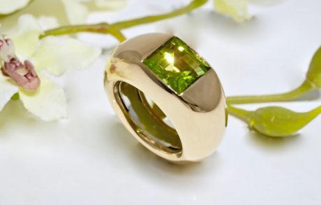 Ein Damenring mit Peridot Kundenstein eingerieben gefasst in Gelbgold und Feder aus 950 Platin