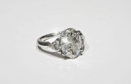 Kundenanfertigung eines Diamantenrings in 950 Platin mit ovalem Diamant und zwei Trillanten als Seitensteine