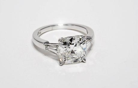 Kissenschliff Diamantenring in 750 Weissgold mit 4 Griff Chaton und seitlich gefassten Trapez Diamanten