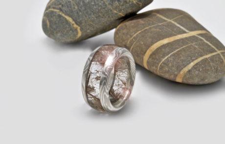 Einzelanfertigung eines Steinkreis Rings geschliffen aus Rutilnadelquarz gefasst in Mokume Gane bestehend aus Silber und Palladium