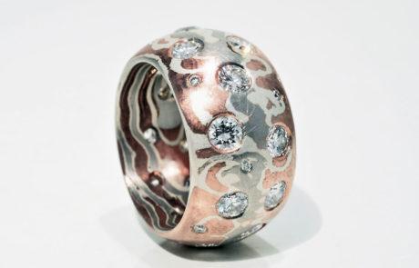 Kundenanfertigung eines Mokume Gane Rings mit Rotgold, Silber und Palladium gewickelt und Kundenbrillanten eingerieben gefasst